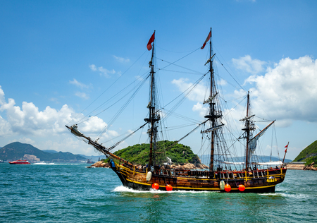 Historic old ship in the ocean near the islands and beautiful panorama