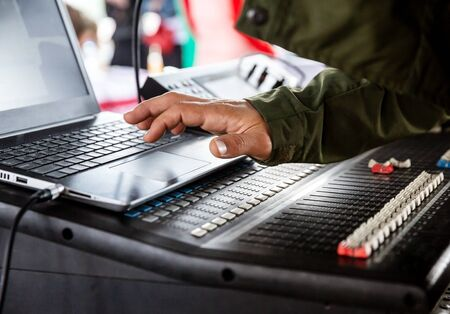 DJs hand over the laptop and mixing console controlling the sound settings
