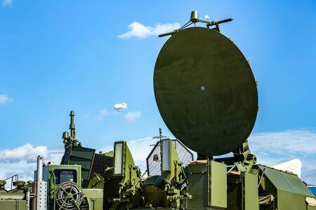 Military radar radio locator station, parabolic antenna on  blue sky