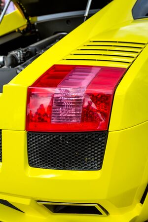 Car rear lights with red backlight and yellow of sport sedan bodywork closeup Stok Fotoğraf - 129641369