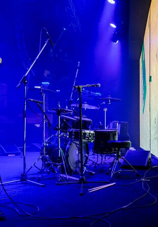 Set of drums and microphones with sound portal on the stage in blue smoke before the concert
