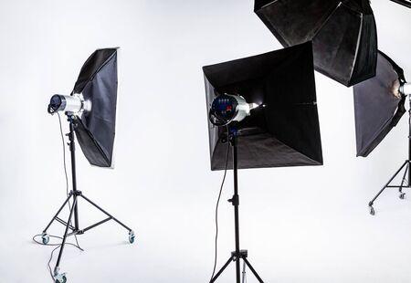 Großes Fotostudio mit Beleuchtungsausrüstung auf weißem Rundwandhintergrund