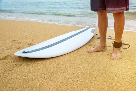 Surfer man stands on sand near the beach with an attached surfboard near the ocean Stock fotó