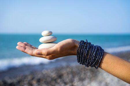 Frauenhände halten Steinpyramide auf der Handfläche auf dem Hintergrund der Küste, des Meeres und des Himmels
