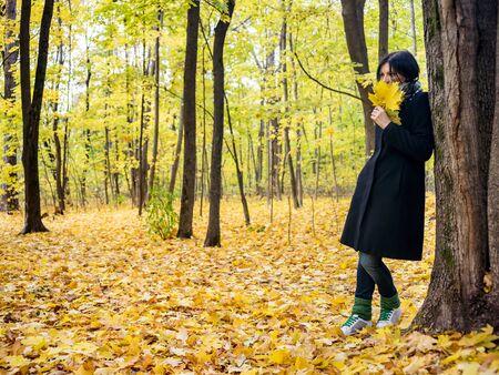 Giovane donna che sogna con un mazzo di foglie autunnali in piedi vicino a un albero nella foresta autunnale