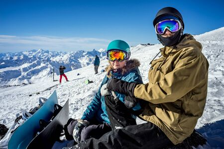 Happy young couple snowboarders on the background high mountains on the winter resort Stock Photo