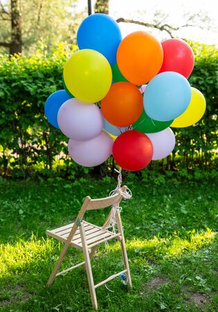 Bunch of colorful balloons, tied to wooden chair on a background of green grass and trees in the park