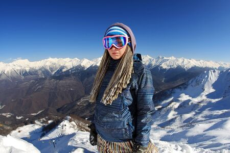 Portrait of young beautiful woman snowboarder on the winter resort