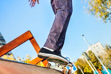 Skateboarder legs before jumping in the halfpipe in skatepark closeup