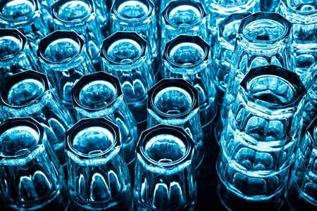 Group of empty clean glasses for water and cocktails upside down on a table in a row in blue tone. Top view in a nightclub under the bar