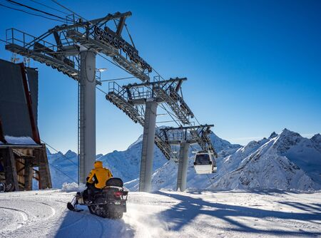 Snowmobile with a driver in motion. Cableway in movement on rise and descent on background beautiful landscape of snowy high mountains Caucasus Elbrus Banco de Imagens