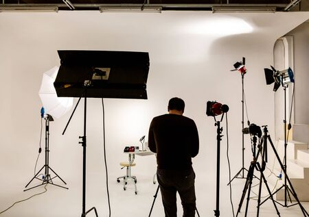 Professional videographer in large photo studio at work. Cyclorama and permanent sources of lighting equipment for video or photo shooting