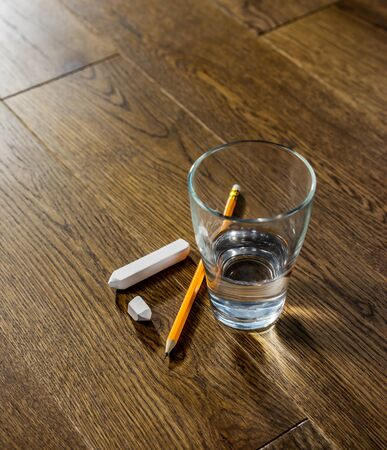 Glass of water and pencil with white chalk on wooden table closeup