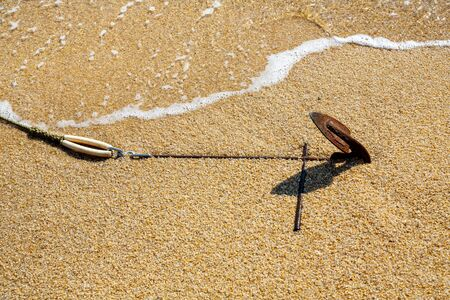 Old rusty anchor of motor boat in the sand on the beach close up Banque d'images