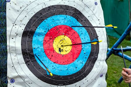 Standard colorful target for archery with arrows. Hand of a man with one arrow after hitting the ten Stock Photo