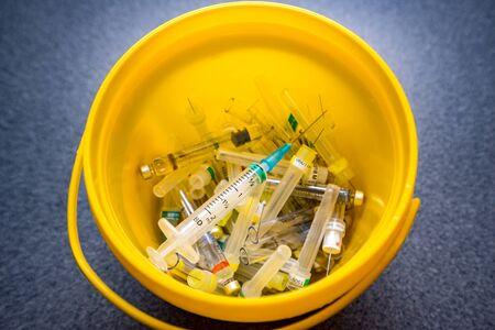 Déchets médicaux, seringues avec aiguilles et flacons vides dans le gros plan du seau à ordures