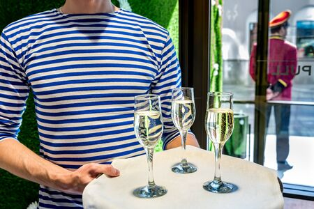 Man waiter in striped vest welcomes guests with glasses of champagne on the event Stock fotó
