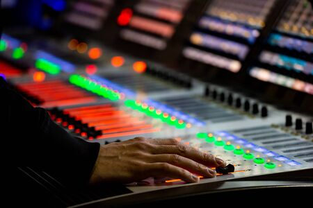 Sound engineer controls the settings on the mixing console panel in sound recording studio for music