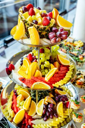 Buffet of ripe fruits on plate close up on festive day at the event