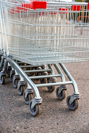 Many empty shopping carts in a row, standing on the outdoor near a supermarket