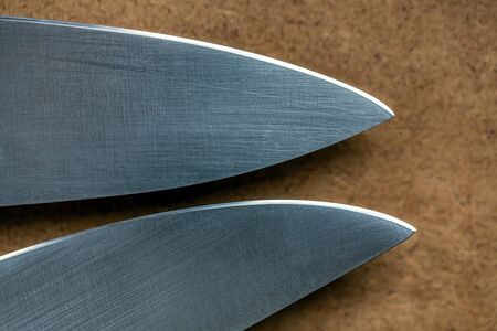 Cutting edge of two kitchen knives closeup. Tips of knives on background of wooden surface