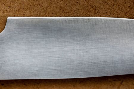 Cutting edge of kitchen knife close up on background of wooden surface Standard-Bild