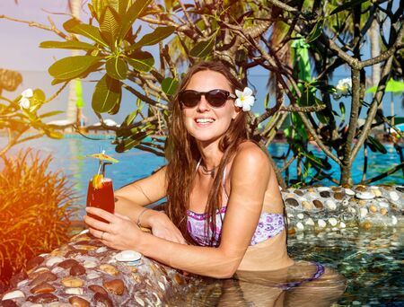Beautiful happy woman with cocktail in pool in hot summer day Standard-Bild