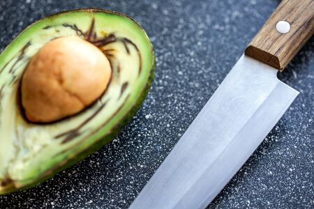 Half an avocado fruit, cut up, lies on the table with kitchen knife closeup on the background