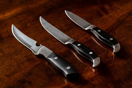 Set of three kitchen knives on wooden table background closeup Standard-Bild