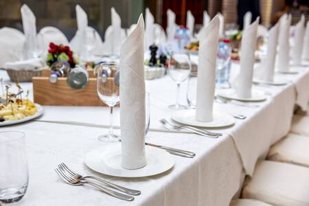 Served banquet table prepared for a conference or a party and covered with a white tablecloth and with a folded cloth napkin on plate