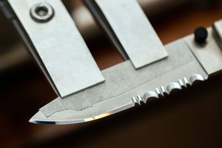 Cutting edge of the knife in the clips on the sharpening device close up