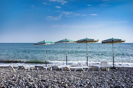 Sunbeds with umbrellas on pebble beach standing along the sea shore on sunny day