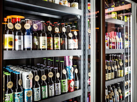 Moscow, Russia - May 18, 2019: Large selection of beer in the fridge behind the glass in the beer bar Editorial