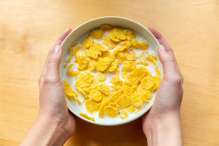 Young girl holds a white plate with milk and delicious corn flakes in two hands on a wooden background close up