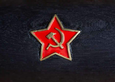 Soviet Red Star icon with symbol hammer and sickle, embedded in a black wooden handle closeup Archivio Fotografico