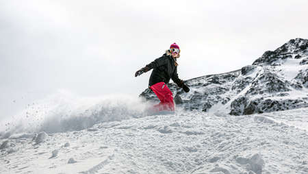 Young woman snowboarder in motion on snowboard in mountains Standard-Bild