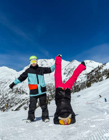 Happy funny couple on the background of snowy mountains. Standing upside down and showing OK sign
