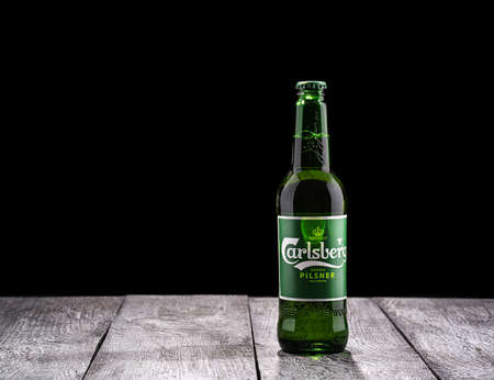 Moscow, Russia - October 1, 2020: Carlsberg pilsner bottle of beer on black background and wooden surface