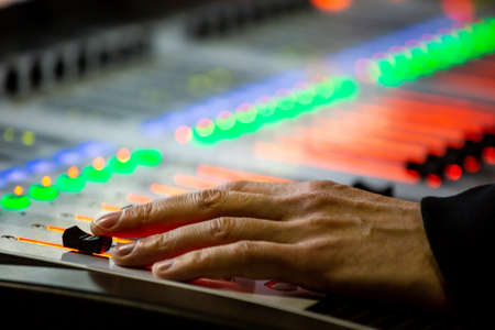Sound engineer controls the settings on the mixing console panel in sound recording studio for music, sound recording, concert activities