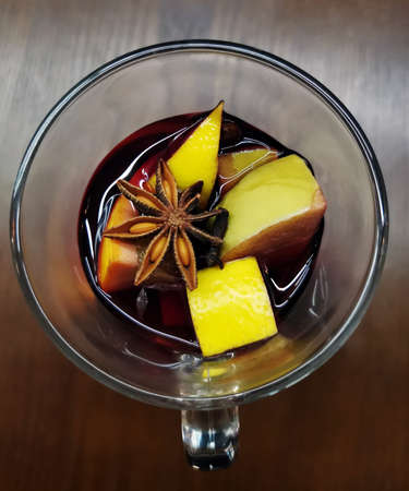 Glass of hot mulled wine with ingredients and spices closeup Standard-Bild