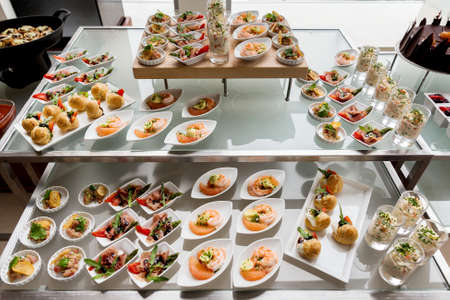 Business lunch at business meeting close up. View of buffet table with different salads and sandwiches in small white plates for quick snack