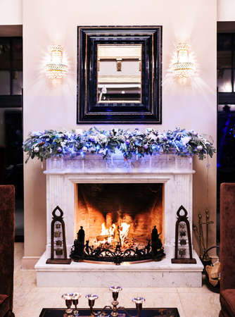 Burning fireplace decorated for Christmas in country house Standard-Bild