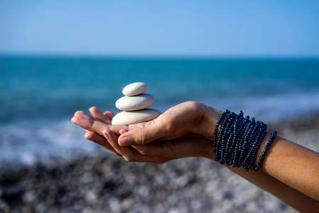 Women's hands holds pyramid of stones on the palm on background of coastline, sea and sky