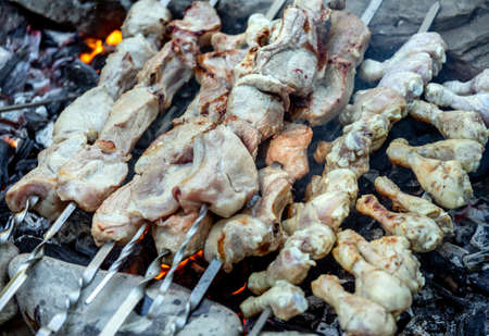 Barbecue on skewers of chicken legs and pork. Picnic in nature cooking on coals after fire