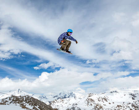 Jumping snowboarder keeps one hand on the snowboard on blue sky background Standard-Bild