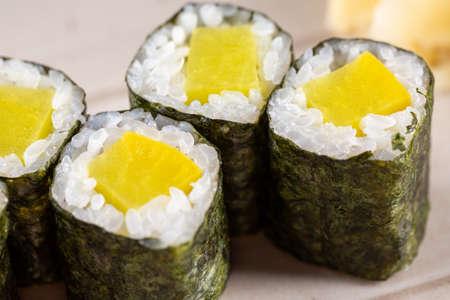 Maki rolls with mango and fresh rice, wrapped in nori on plate closeup Standard-Bild
