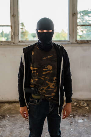 Armed criminal posing for a photo in the abandoned building.