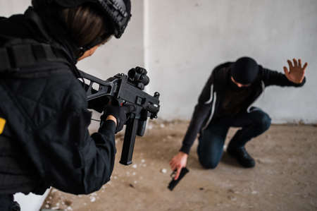 Police woman, swat member arresting armed criminal in the abandoned building. Imagens