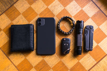 EDC setup. Concept on the wooden chess board. Everyday carry for a man. Knife, Multitool, Flashlight, Car key, Paracord bracelet, Wallet, Lighter, Smartphone...