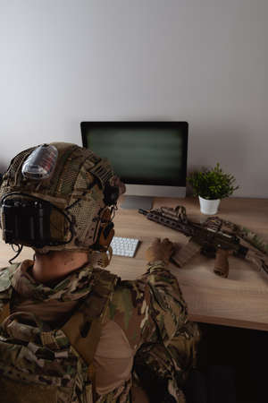 US Army special forces operator looking at the computer screen. Seal team operator in full gear.